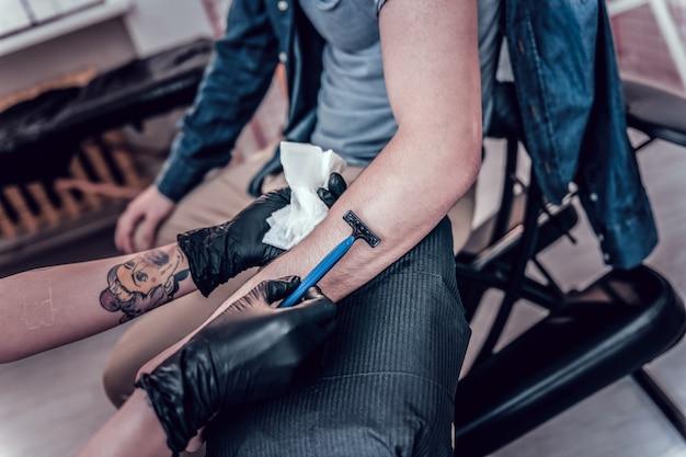 Rendendolo liscio. maestro del tatuaggio che trasporta il rasoio usa e getta e lo usa per la futura area del tatuaggio a portata di mano