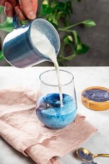 Fare il latte dal tè blu matcha nuovo superfood alla moda cibo sano foto verticale