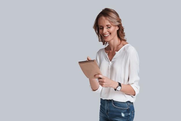 Prendere appunti. bella giovane donna in abbigliamento casual che scrive qualcosa e sorride mentre sta in piedi su uno sfondo grigio