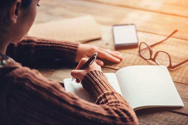 Prendere appunti. immagine ravvicinata di una donna che scrive su un taccuino con spazio per le copie mentre è seduta al tavolo di legno grezzo