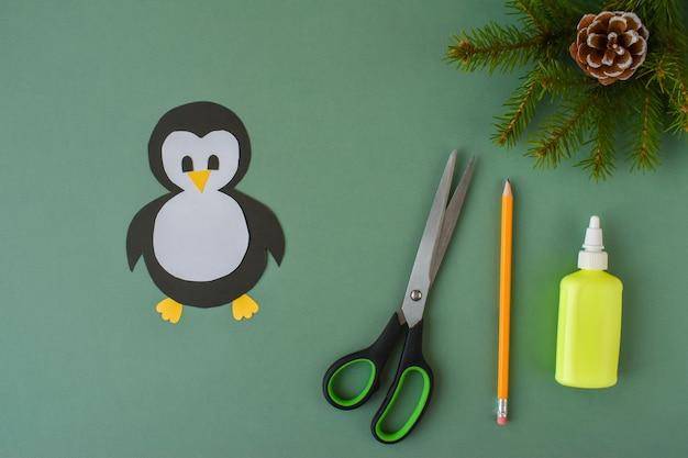 Fare un pinguino con carta colorata. passaggio 3. incolla le parti del pinguino. il pinguino è pronto.