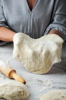 Fare il processo della pizza, mano della donna che lavora con pasta e farina