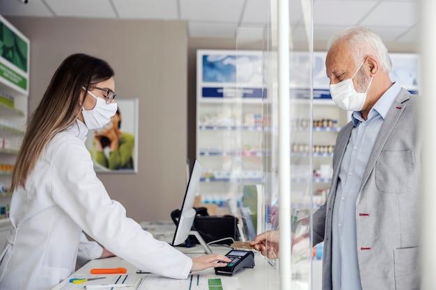 Fare una ricetta in farmacia e pagare il conto con una tessera, vendere medicinali. un uomo maturo fa scorrere una carta e paga i farmaci ai farmacisti. maschera facciale protettiva durante il coronavirus