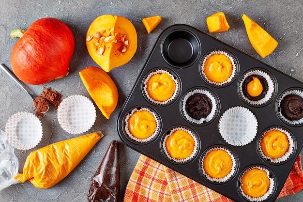 Preparare muffin alla zucca per la festa di halloween. ingredienti sullo sfondo, vista dall'alto