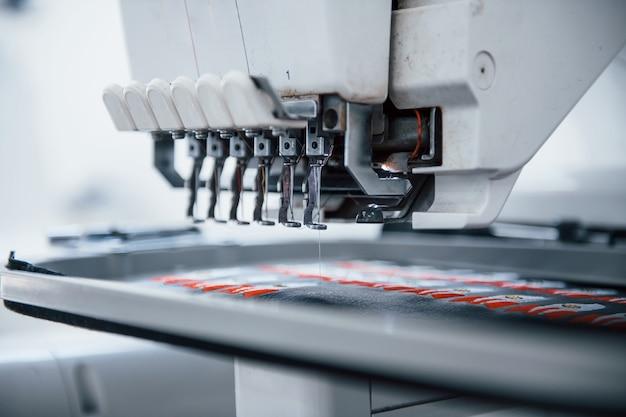 Fare immagini di razzi. vista ravvicinata della macchina da cucire automatica bianca in fabbrica in azione.