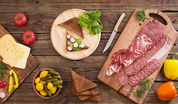 Fare panini con carne e salsiccia sul tavolo di legno
