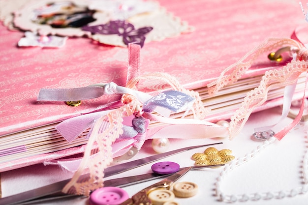 Fare album di scrapbooking con anelli e decorazioni sul tavolo e strumenti