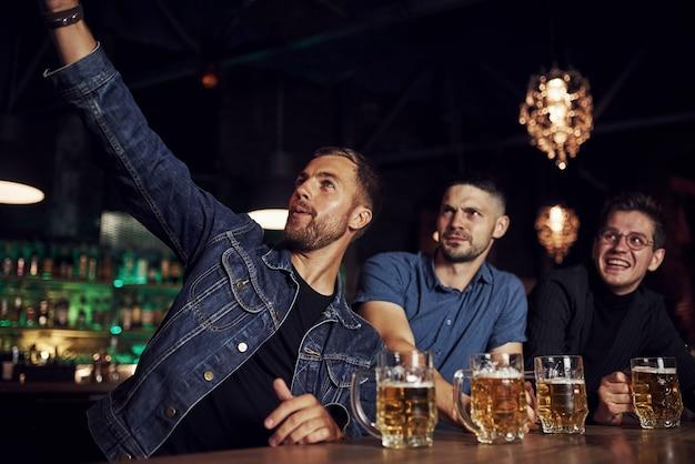 Fare selfie. tre appassionati di sport in un bar a guardare il calcio. con la birra in mano.