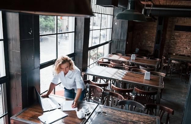 Fare alcune note. donna di affari con capelli biondi ricci all'interno in caffè durante il giorno.