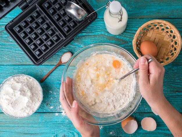 Preparare i waffle a casa - piastra per cialde, pastella nella ciotola e ingredienti - latte, uova e farina.