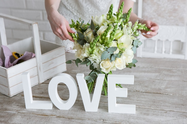 Fare mazzo di nozze nel laboratorio di floristica. irriconoscibile fiorista che assembla un tenero bouquet di rose bianche, alloro fresco e fiori di campo. decorazione o bellissimo regalo per una donna adorabile.