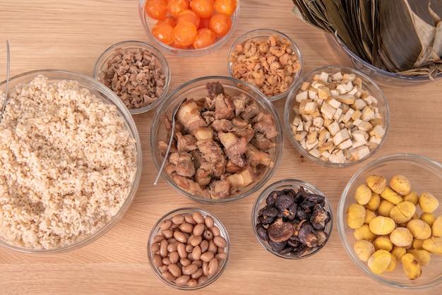 Fare zongzi - ingrediente dello zongzi cinese di gnocchi di riso che fa sul tavolo a casa per la celebrazione del dragon boat festival, primo piano, stile di vita.
