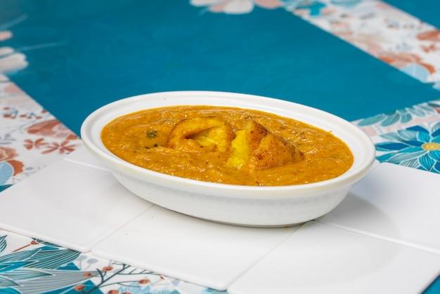 Malai kofta curry sulla ciotola a sfondo bianco. malai kofta è un famoso piatto di cucina indiana con patate, paneer e polpette fritte di formaggio in salsa di pomodoro cipolla con spezie indiane piccanti