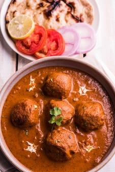 Malai kofta curry - piatto classico dell'india settentrionale. alternativa vegetariana alle polpette servite con roti tandoori o pane indiano e insalata verde, messa a fuoco selettiva