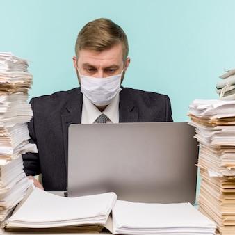 Un ragioniere maschio o un dirigente aziendale lavora in un ufficio in una pandemia in considerazione del lavoro di ufficio accumulato. una maschera medica protettiva è sul viso. sul desktop ci sono grandi pile di documenti.