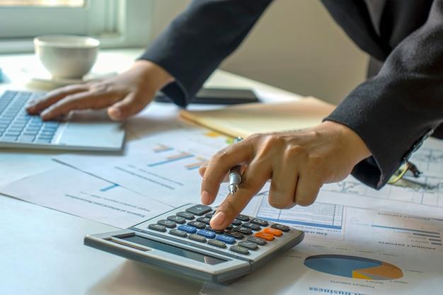 I ragionieri maschi stanno lavorando su documenti finanziari e calcolatrici per spese aziendali e finanziarie.
