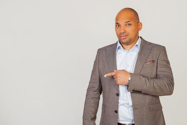 Uomo d'affari afroamericano maschio in una giacca che punta con la mano e il dito con un'espressione di disgusto. copia spazio. su uno sfondo grigio.