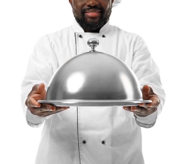 Chef afro-americano maschio con vassoio e cloche su sfondo bianco