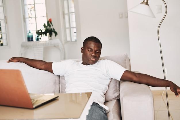 Uomo afroamericano maschio che riposa a casa, dormendo sul divano