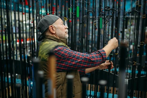 Pescatore maschio che sceglie canna nel negozio di pesca.