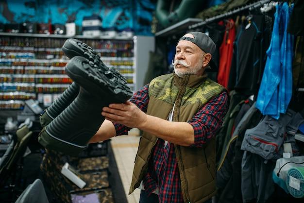 Pescatore maschio che sceglie stivali di gomma nel negozio di pesca.