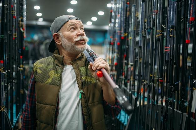 Il pescatore maschio tiene la canna nel negozio di pesca. attrezzature e strumenti per la pesca e la caccia, scelta di accessori in vetrina in negozio, assortimento di filature e telescopi