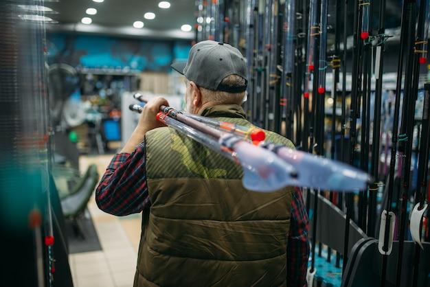 Il pescatore maschio tiene la canna con la bobina nel negozio di pesca.
