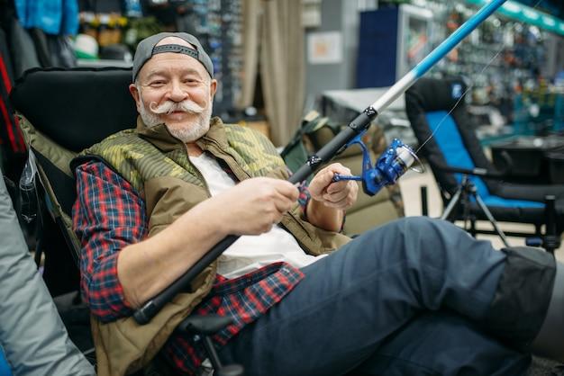 Pescatore maschio con asta seduto in poltrona, negozio di pesca.