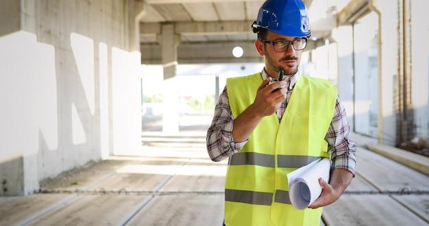 Architetto maschio che comunica sul walkie-talkie al cantiere