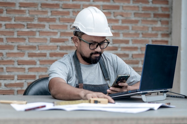 Architetto o ingegnere maschio con casco bianco che lavora a casa guardando il telefono