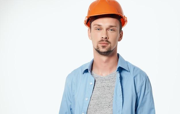 Architetto maschio in cappello duro arancione che lavora vista ritagliata grigia
