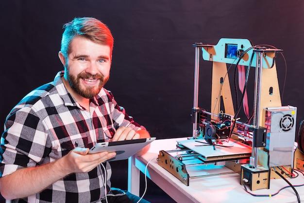 Architetto maschio utilizzando la stampante 3d in ufficio.