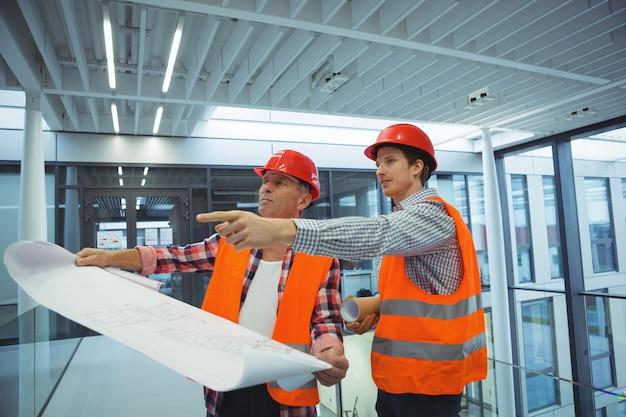 Architetti maschi che discutono sulla cianografia nel corridoio