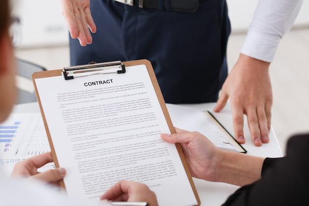 Braccio maschile in camicia offre forma di contratto negli appunti