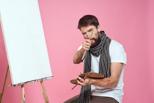 Artista maschio dipinge su cavalletto