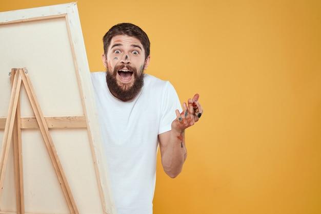 L'artista maschio sta davanti alle emozioni del cavalletto che disegnano il giallo di approccio creativo.