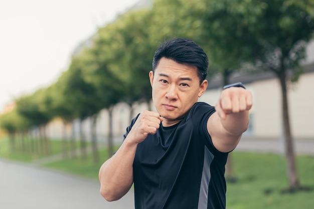 L'atleta asiatico maschio dimostra il rack di boxe durante il jogging mattutino e il fitness