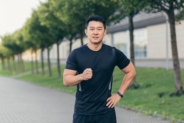 Atleta maschio asiatico, felice del risultato della corsa mattutina, corre nel parco vicino allo stadio