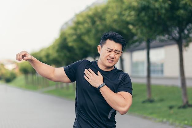 Atleta maschio asiatico, dolore alla spalla impastato, muscoli doloranti delle braccia nel parco