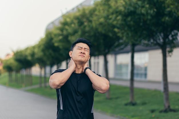 Atleta maschio asiatico, correndo nel parco in uno zaino prima del lavoro, correndo nel parco vicino allo stadio ha un forte dolore al collo stanco del dolore