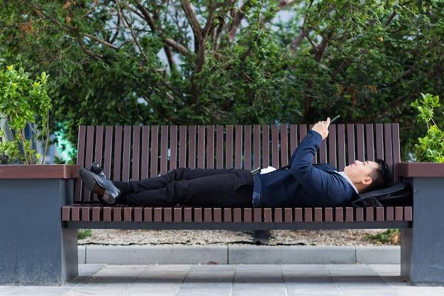 Uomo d'affari asiatico maschio sdraiato su una panchina e riposato dopo il lavoro usa un telefono cellulare per corrispondere e leggere le notizie