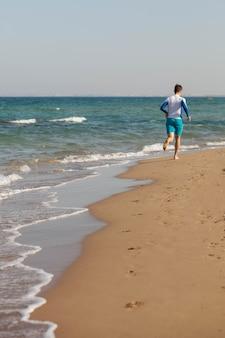 Un atleta maschio corre lungo la spiaggia in pantaloncini blu lungo la costa del mare di cipro copia spazio