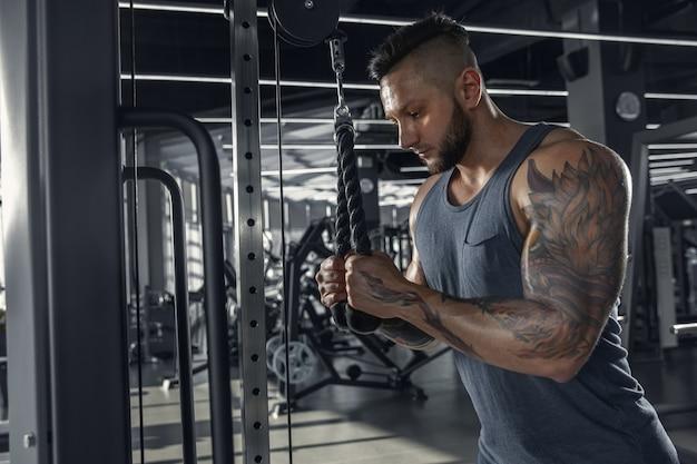L'atleta maschio che si allena duramente in palestra
