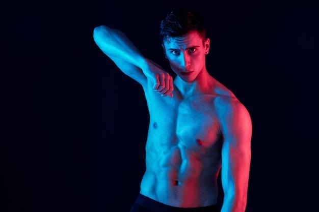Atleta maschio con muscoli pompati e un torso su sfondo nero