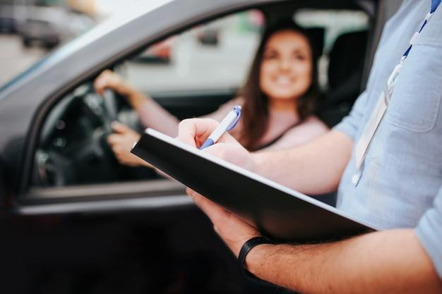 L'istruttore automatico maschio prende l'esame in giovane donna. modello vago che si siede in automobile e che si tiene per mano sul volante. guy tenere cartella con carta nelle mani.