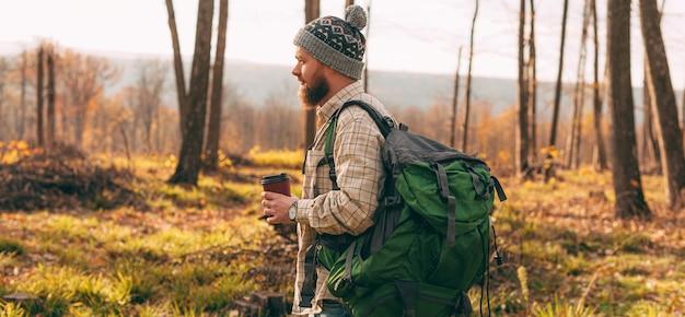 Zaino in spalla maschio che cammina nella foresta di autunno