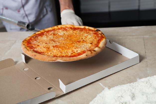 Fornaio maschio che prepara la pizza per la consegna