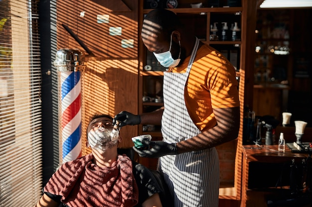 Barbiere maschio in maschera medica che applica crema da barba sul viso dell'uomo
