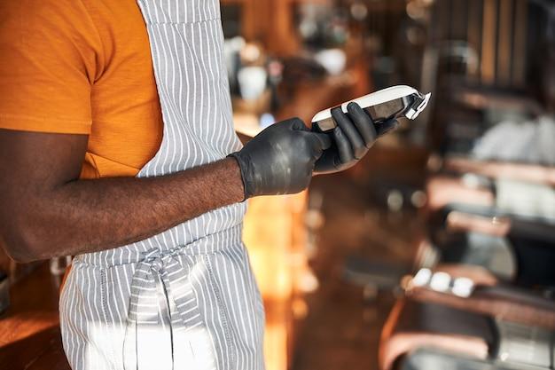 Barbiere maschio in guanti sterili che tengono la macchina da barba elettrica