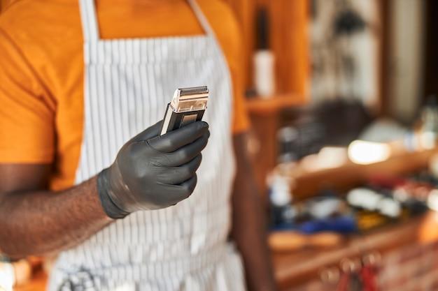 Barbiere maschio in guanti sterili che tengono tagliacapelli portatile